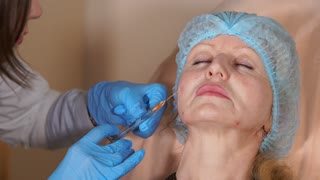 A plastic surgeon in a private clinic injects the cannula into the neck of a middle-aged woman, the drug fillers are in a syringe with a long needle that the doctor moves to the sides.