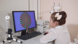 a portrait of a child who looks at a computer that is in the office of a pediatric ophthalmologist, the child determines the level of color perception for further treatment
