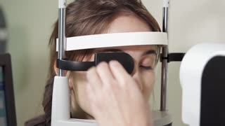 a portrait of a teenager in the ophthalmologist's office, a woman undergoes an Ophthalmoscopy for the study of the vascular membrane, the retina, the optic nerve