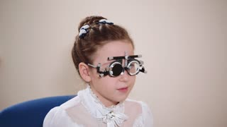a portrait of a teenager who checks the eyes of an ophthalmologist, the physician uses a visionometry, an ophthalmologist uses special glasses to adjust the clarity