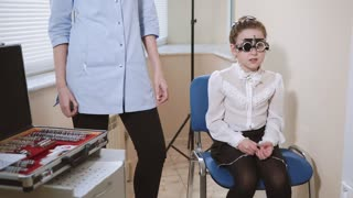 a portrait of a teenager who checks the vision with the help of visionimetry, an ophthalmologist stands next to her, the girl checks the clarity of vision with the help of a vidiometry