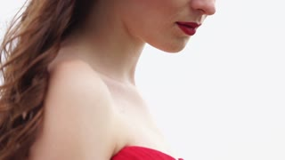 a portrait of a young and pretty woman with bright black make-up, a lady dressed in a red dress and has a scarlet lipstick, she looks thoughtful and mysterious