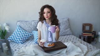 A pretty woman dressed in pajamas takes breakfast buns and drinks tea and milk in the bedroom on the bed. A woman enjoys food, covered herself with a blanket and holds a tray for eating in her legs.