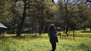 a professional photographer who works as a reporter takes pictures of the beauty of a local nature reserve, a woman presses a button of a gadget among a flowering garden