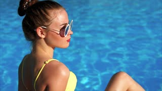 A profile of a young and pretty woman in sunglasses, who sits by the pool and sunbathes on a summer day in a stylish swimsuit, the pool water shines in the background