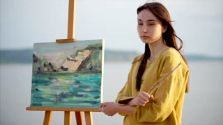 A romantic adult girl stands near her still life next to the sea or river, the artist painted a landscape on the canvas that stands on the easel, in her hands a brush and palette