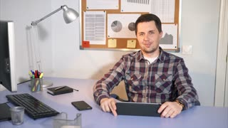 A smiling man looking at the camera sitting in his office. There is a different gadgets on his work place. He use it for a better and faster work with clients.