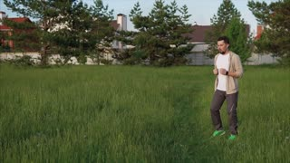 A sports man does an active warm-up in the park area, he jumps and runs on the spot, in order to begin physical training with warmed muscles
