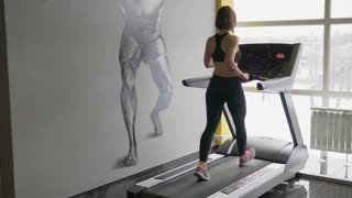 A sports woman is engaged in walking on a treadmill in a fitness club. The athlete warms up the muscles before starting cardio training, in order not to pull the tendons.