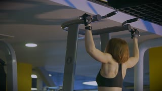 A sporty woman with stretchable gloves makes the whole body pull up on the bars in the sports club. She actively and methodically climbs up, strengthening the shoulder complex.