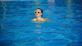A stylish and joyful girl in fashionable glasses swims in an outdoor pool on a hot summer day, a lady enjoys cool water on her vacation