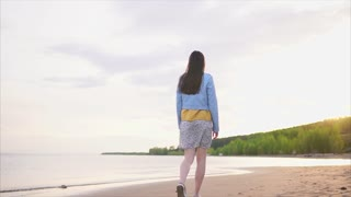 A thin teenager with long hair in modern clothes strolls along a deserted shoreline with wet sand, the girl slowly walks along the beach near the sea or the river