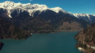 a view of the majestic high mountains with snowy peaks, at the sandy bottom there are a blue lake and human buildings for outdoor holidays