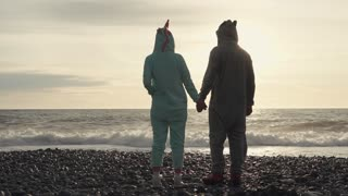a woman in a kigurumi suit watching the waves during sunset, husband and wife holding hands and enjoying the sea view and coastal waves