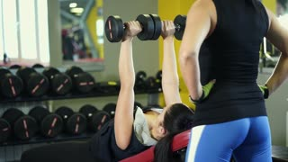 A woman insures another athlete who is engaged with a dumbbell in a fitness club. A woman helps to monitor the position of the hands during exercise to load the triceps and biceps.