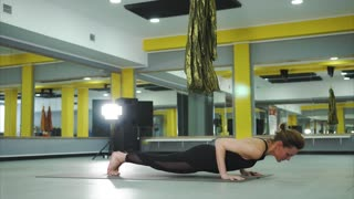 A woman performs asana, which is called a dog face up. The yog pulls his chin up, pushing his hands away from the floor, elbows looking forward, the fingers are placed in different directions