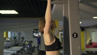 A woman performs exercises for the development of muscular muscles by lifting the body on a simulator. The athlete develops pectoral muscles, as well as the muscles of the back.