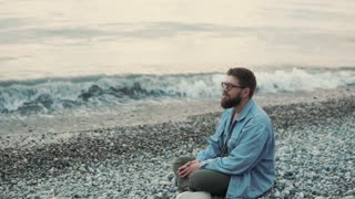 a young and bearded man sits on a stony beach in a wilder time, the jennelman enjoys the sea view and looks into the distance, the waves beat on the shore