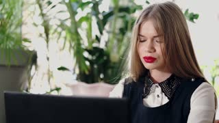 A young and beautiful business woman is browsing the latest stock news on the Internet on a laptop. A girl with red lips is focused on her work, she is looking for the necessary business information