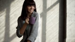 a young and beautiful woman drinks a hot drink of their glass, the lady holds a cup of tea in her hand and smiles while drinking tea, she enjoys a hot and tasty drink