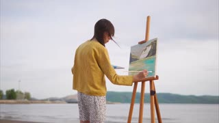 A young and creative artist paints a picture on a canvas in an open air, a woman paints a brush on the canvas, which stands on an easel in the nature