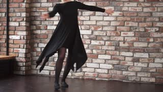 a young and elegant woman in a black dress rehearses a dance in a free style, a dancer swirling around with her hands up, mentally coming up with the next movement