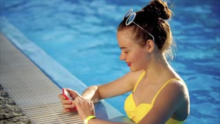 A young and embroidered woman who wore a swimsuit is in the pool with cool water, a beautiful woman looks at photos on a mobile phone for social networks