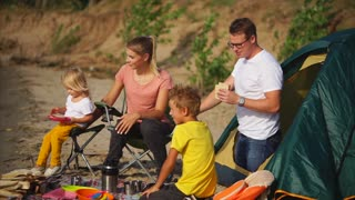 A young and friendly family, arranged dinner in the daytime in nature, the wife takes care of her daughter and sits on a chair next to her children, the husband is in a tent and eats a sandwich