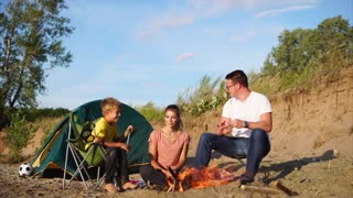A young and friendly family who spend vacations in nature, sit near the fire and tents with their son, parents talk with the child, mother is happy in the camping zone near the fire
