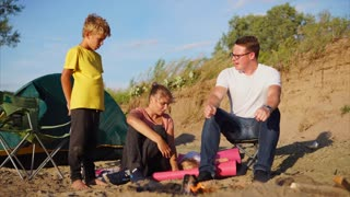 A young and friendly family who spend weekends in nature, sit near a campfire and a tent with their son, mother sits on a sandy beach, a boy stands and looks at the fire the husband talks to the child