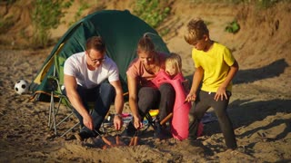 A young and happy family who rests on a sandy beach with a tent frying meat sausages on skewers on fire, mom holding her little child, next to sit a son and husband who cooks dinner in the open air