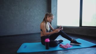 A young and pretty business lady who is engaged in the gym checks incoming messages on a mobile phone, a spirt sitter sits on a yoga mat