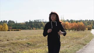 A young and pretty woman in a sports suit is practicing in nature, a lady runs through the park in the summer to maintain a good physical shape