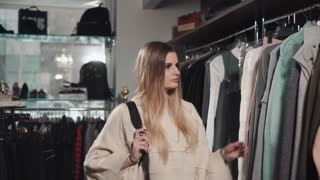 a young and pretty woman looks at clothes, a lady wants to update her wardrobe before the new season, she carefully studies the range offered by the store