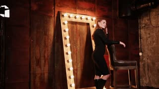 a young and pretty woman who is dressed in a black dress posing in an underground place, a lady stands near a chair and a wooden frame with light bulbs