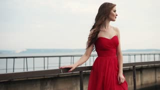 a young and pretty woman who looks gently and romantically at a pier near the ocean on a summer day, her dress fluttering under the winds, she has curly brown hair on her head
