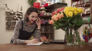 a young and pretty woman works as a florist in a flower shop, a lady holds a smartphone in her hand and talks to her client, a flower business master stands near a laptop and roses in a vase