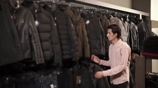 a young and thin man considers winter jackets in a clothing store, a man carefully studies the quality of fabrics, maybe he wants to pick up quality and stylish clothes