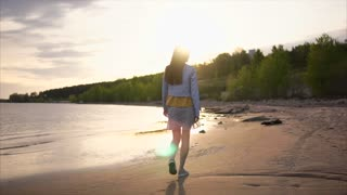 A young and thin woman with long hair slowly walks at sunset along the coastline along the river or lake, nearby there is a forest, on the street a warm summer