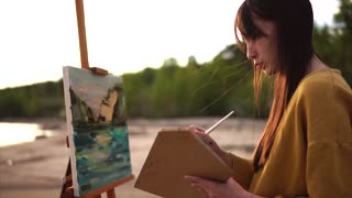 A young artist draws a palette knife still life, a girl creates a work of art near the sea or river. Person placed Malbert in the open air in order to draw from nature