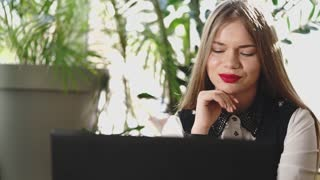 A young beautiful woman enjoys reading letters from fans who have written to her email. Woman with painted lips looks at laptop monitor and smiles.