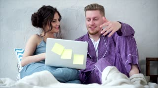 A young couple who watch a merry comedy on a laptop rest in the bedroom sitting on the bed. Smiling man and woman dressed in homemade pajamas