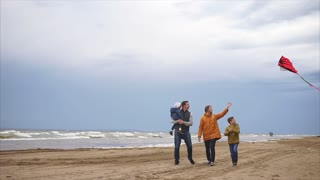A young family walks along the beach next to the sea in cold weather, the son is holding a kite in his hands, the father carries a child, the mother is happy with a good weekend