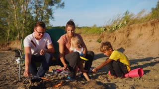 A young family who came to a sandy beach in order to relax with a tent in nature, fry meat sausages on fire, mom holds her little child, next to her son and husband