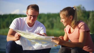 A young family who came to rest create a map of the area for travel, they look at the paper map, people are in a tent near the lake, the couple are talking to each other
