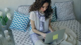A young fashionable blogger writes a new article on a laptop sitting in a bed in the bedroom. A woman who covers her feet with a blanket, who wears stylish pajamas prints the text.
