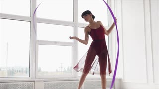 a young gymnast is trained to dance with a ribbon, a winding ribbon deftly follows the movement of a woman, a lady demonstrates a complex combination of plastics and dance