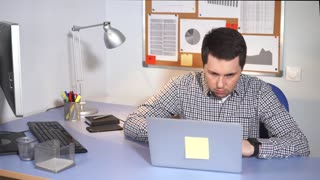 A young IT specialist who sits at a computer desk looks at the laptop screen for the work done by him. A man likes to be part of a corporate team and take part in projects