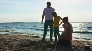 A young man and his son are lighting a fire, the wife is holding a child and taking care of him, the family is spending vacations in nature on a summer day