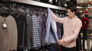 a young man chooses a fashionable shirt, the person is in an exclusive boutique, he carefully chooses festive clothes for the renovation of the wardrobe
